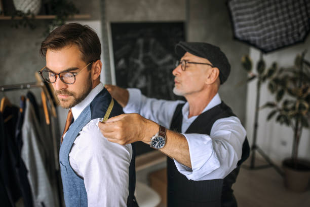 Professional tailor taking back measurements for a suit stock photo