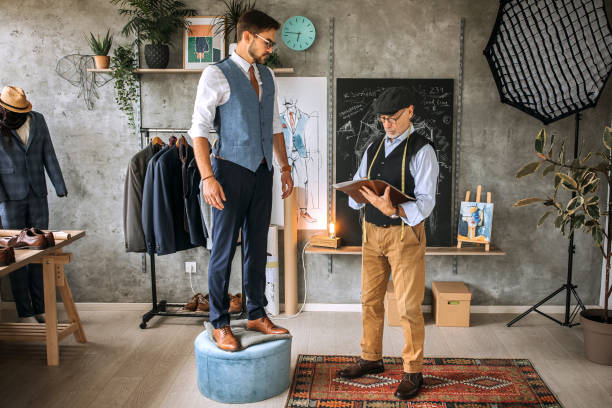 Professional tailor taking measures for a suit stock photo