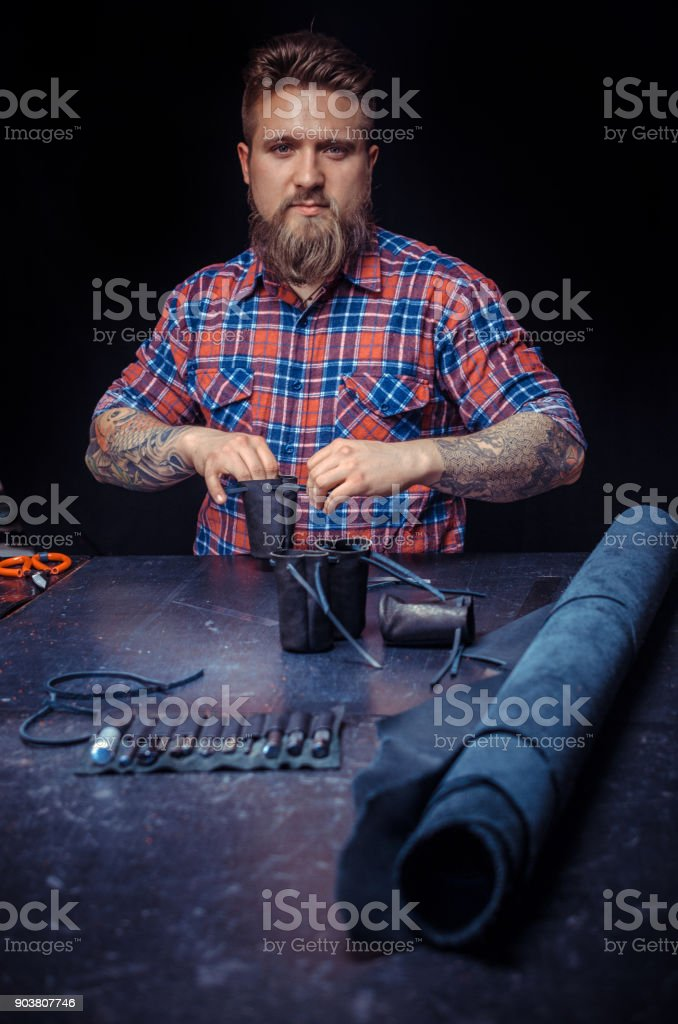 Professional Tanner cuts out leather goods stock photo