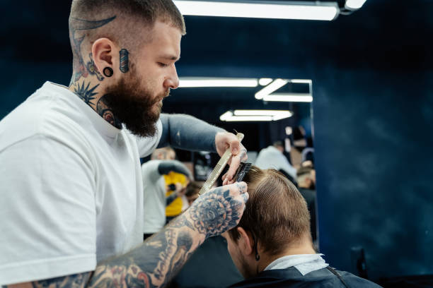 Professional tattooed barber using cutthroat razor cutting hair. Attractive male is getting a modern haircut in barber shop. Close up Professional barber with open cutthroat razor shaves hair on man's temples. cutthroat stock pictures, royalty-free photos & images
