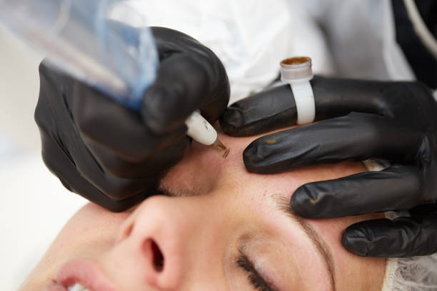 professional tattooist making eyebrow make up stock photo