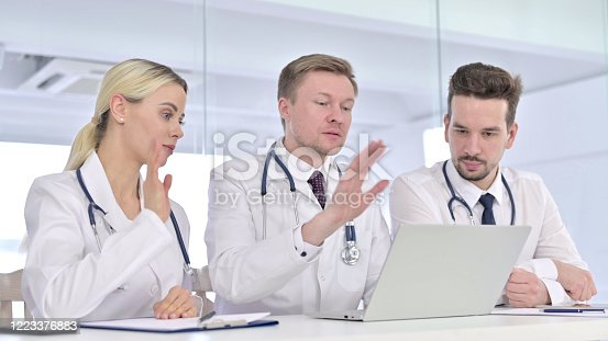 944493796 istock photo Professional Team of Doctors doing Video Chat on Laptop 1223376883