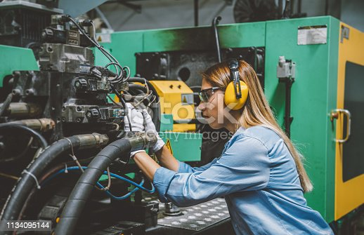 Side view portrait of young female technical repair engineer employee operating a production line industrial CNC machine and testing, installing, analyzing and fixing bolts it with hand tools for work at a modern factory plant building. XXXL