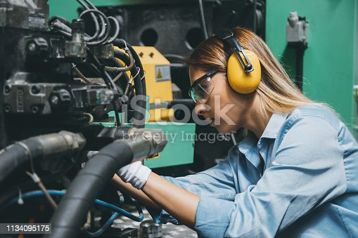 Close up side view portrait of young female technical repair engineer employee operating a production line industrial CNC machine and testing, installing, analyzing and fixing bolts it with hand tools for work at a modern factory plant building. XXXL