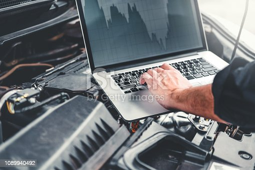 istock Professional Technician Hands of checking car engine repair service using laptop on car 1089940492