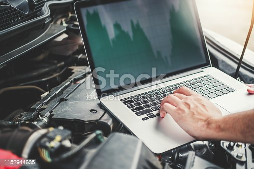 istock Professional Technician Hands of checking car engine repair service using laptop on car 1152944635