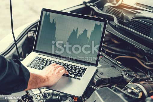 istock Professional Technician Hands of checking car engine repair service using laptop on car 1169928068
