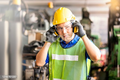 istock Professional technicians wear protective equipment and hard hats in large industrial plants. Protective and Safety Equipment eye wear, ear plug, vis clothes and protective helmet. 1215761037