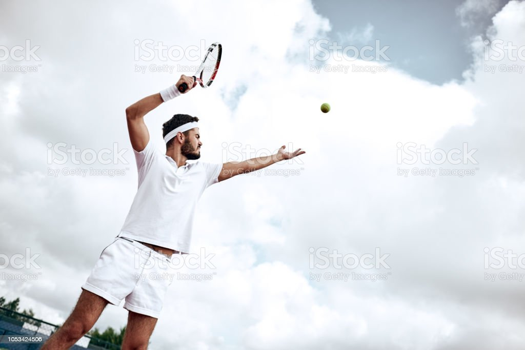 Professional tennis player playing a game of tennis on a court. He is...