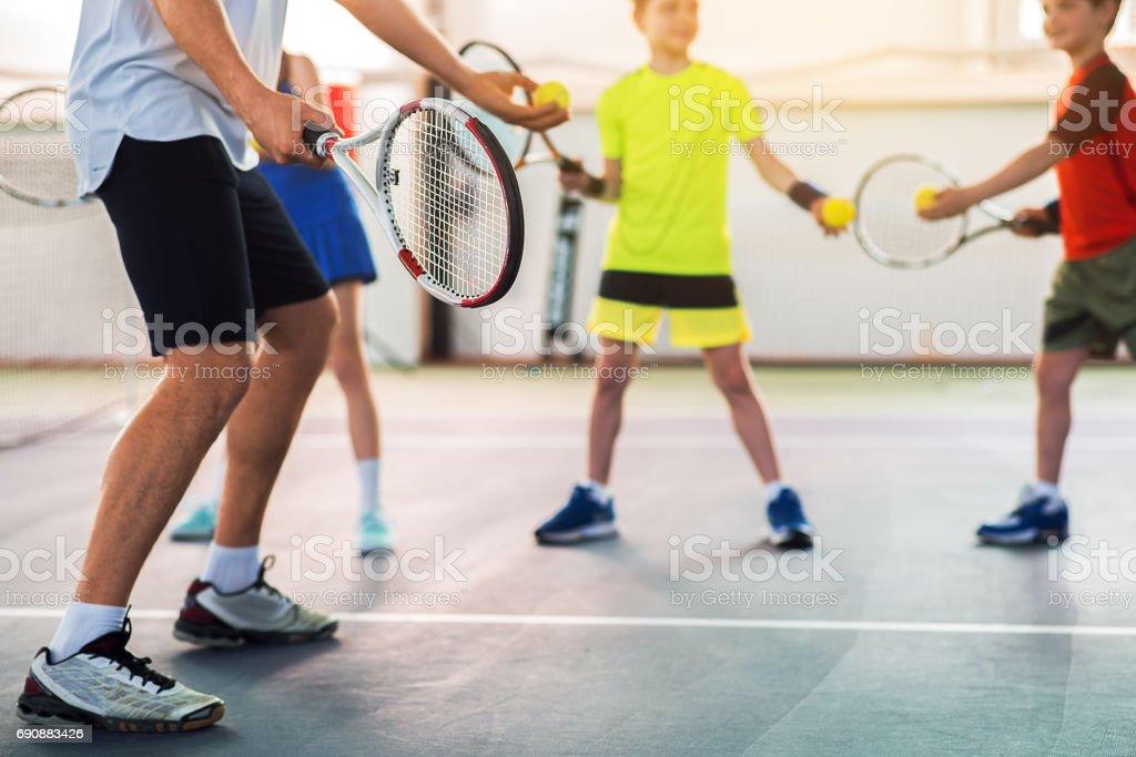 Professional tennis player teaching kids stock photo