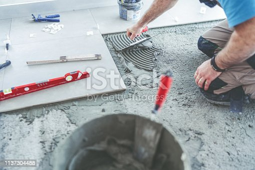 Tile worker spreading and smoothing adhesive on the floor before installing tiles