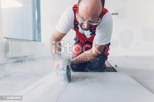Mid-thirties tile mason cutting tile with circular cutting tool
