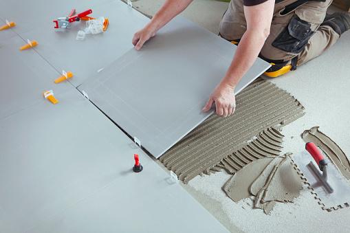 Professional tiler installing new tiles on the floor.