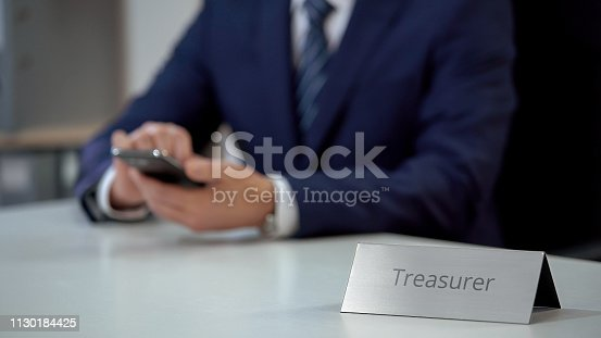 Professional treasurer using smartphone, planning costs and revenues of company