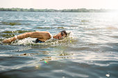 Professional triathlete swimming in river's open water. Man wearing swim equipment practicing triathlon on the beach in summer's day. Concept of healthy lifestyle, sport, action, motion and movement.