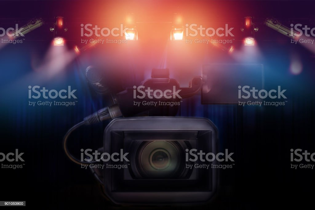 professional video camcorder with set of light hanging in television studio background. stock photo