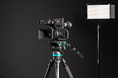 Professional video camera on camera tripod and two lighting LED panel on black background. The picture is taken with Sony A7III camera.