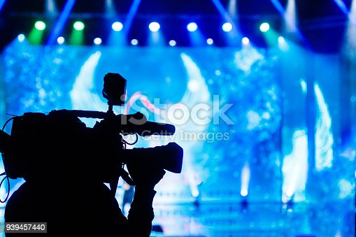 istock Professional Video camera operator working with his equipment, blue background 939457440