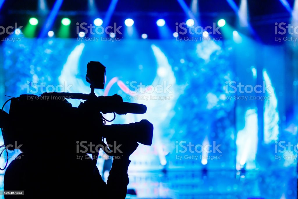 Professional Video camera operator working with his equipment, blue background stock photo