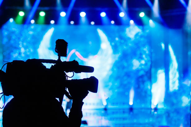professional video camera operator working with his equipment, blue background - arts culture and entertainment stock pictures, royalty-free photos & images