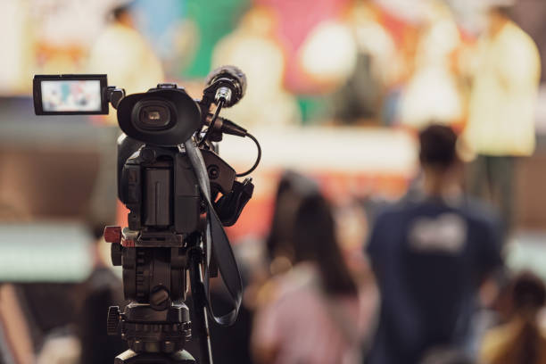 Professional video camera with abstract blurred background Professional video camera with abstract blurred background producer stock pictures, royalty-free photos & images