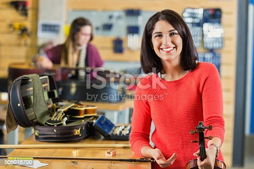 Mid adult woman is looking at the camera and smiling. Professional musician is holding a violin that she purchased fromm a small local business that sells and repairs musical instruments. Violinist is standing next to check out counter. Instrument case is on counter next to her.