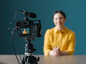 istock Professional vlogger sitting in front of a camera 1211311209