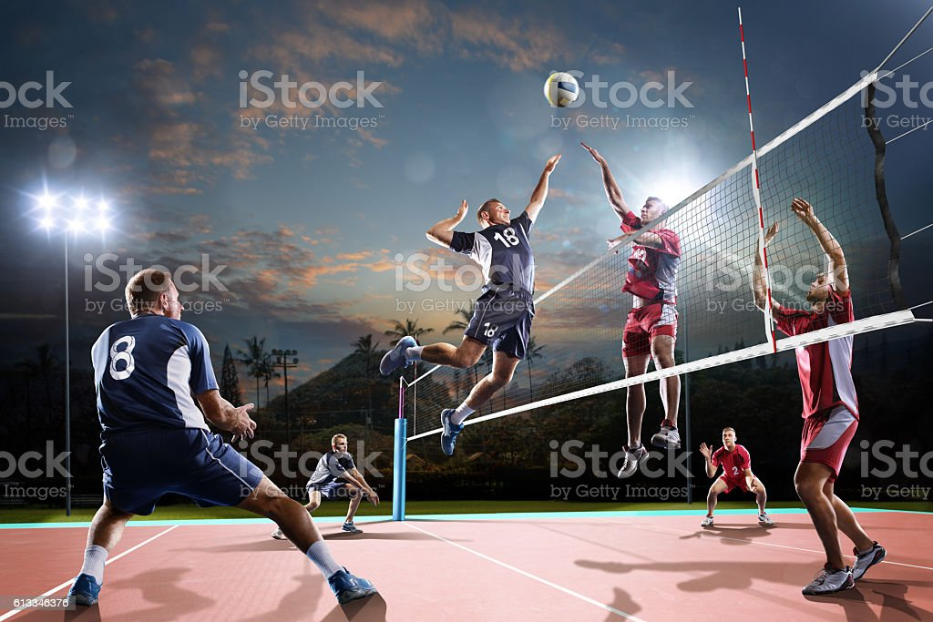 Professional volleyball players in action on the night court stock photo