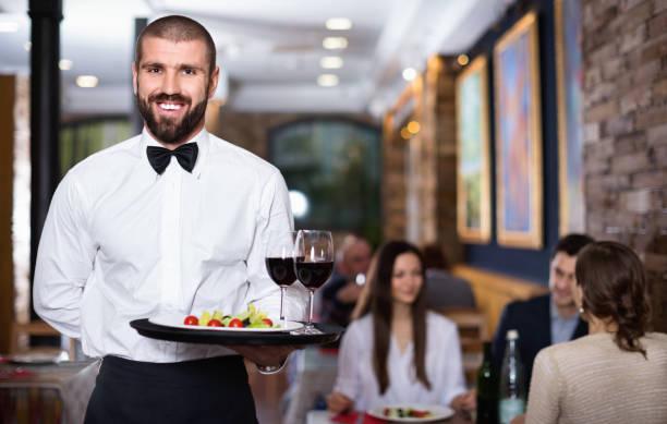 Professioneller Kellner mit Serviertablett für Restaurantgäste – Foto
