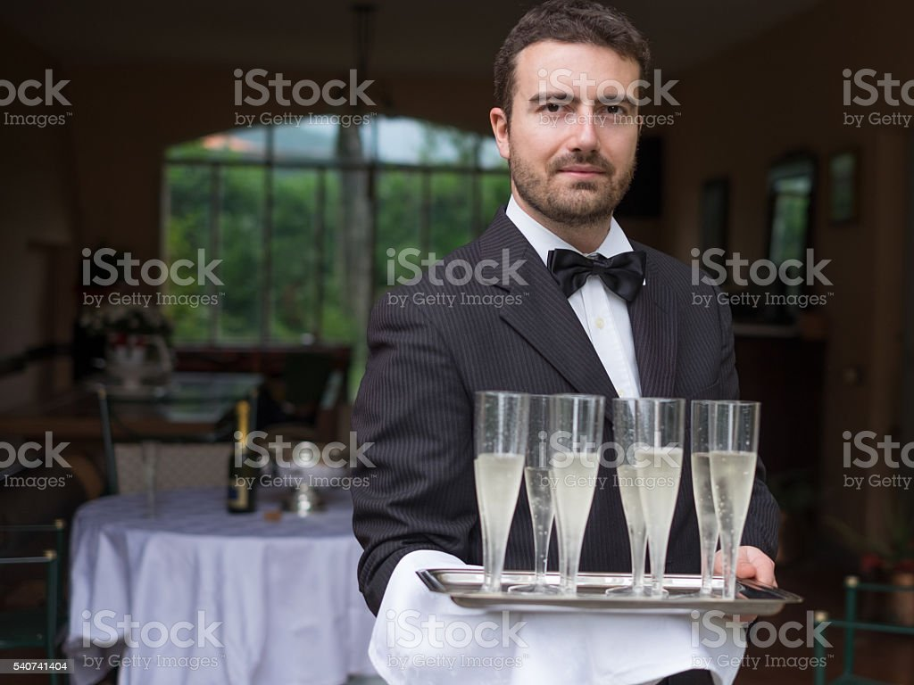 Professional waiter in uniform is serving champagne stock photo
