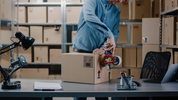professionele warehouse worker controles en seales karton box klaar voor verzending. in de achtergrond die werkzaam is in de rijen van planken met kartonnen dozen met bestellingen klaar. - warehouse worker stockfoto's en -beelden