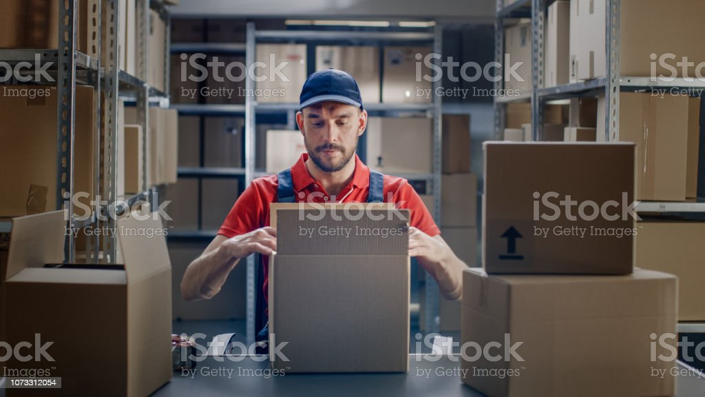 Professional Warehouse Worker Finishes Order, Sealing Cardboard Boxes...