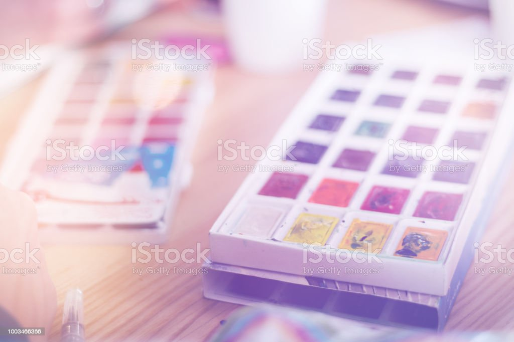 Professional watercolor aquarell paints in box with brushes on old wooden board, light toning stock photo
