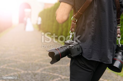 Professional wedding photographer takes pictures of the bride and groom in garden, the photographer in action with two cameras on a shoulder straps