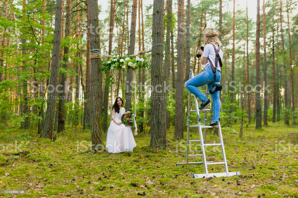 Professional wedding photographer using stepladder to make pictures of the bride stock photo
