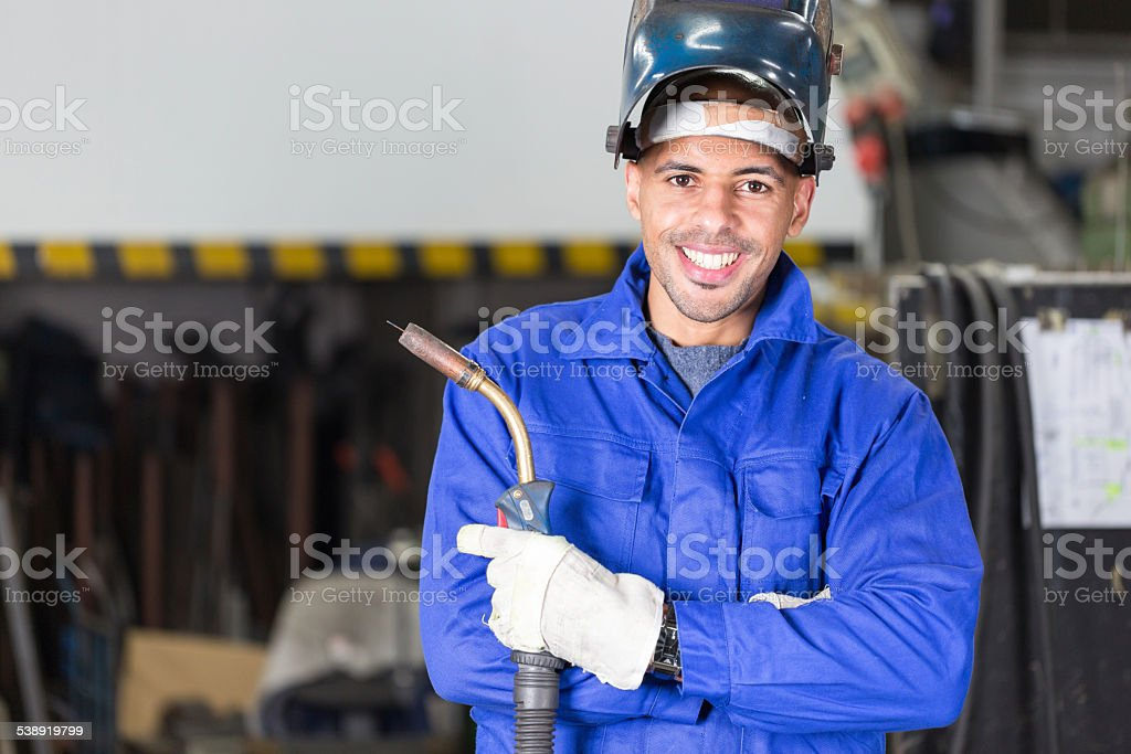 Professional welder posing with wellding machine stock photo