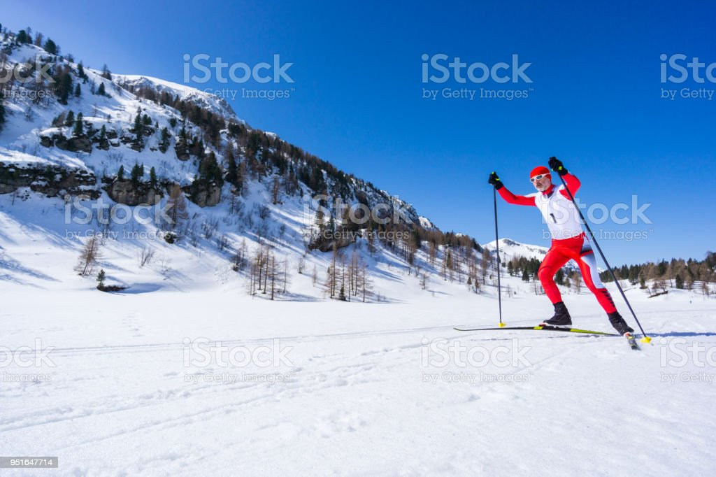 competitive cross country skier in race outfit with start number...