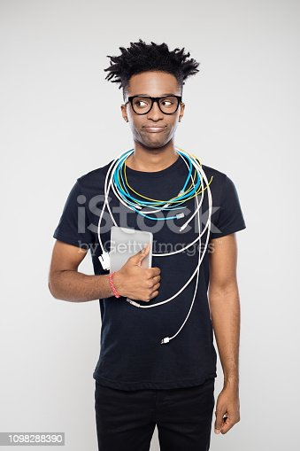 Portrait of nerdy afro american IT professional with cables around neck and digital tablet in hand looking away against gray background