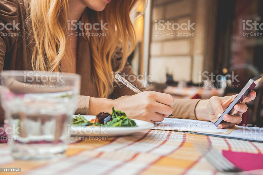 Professional woman filling documents at the restaurant stock photo