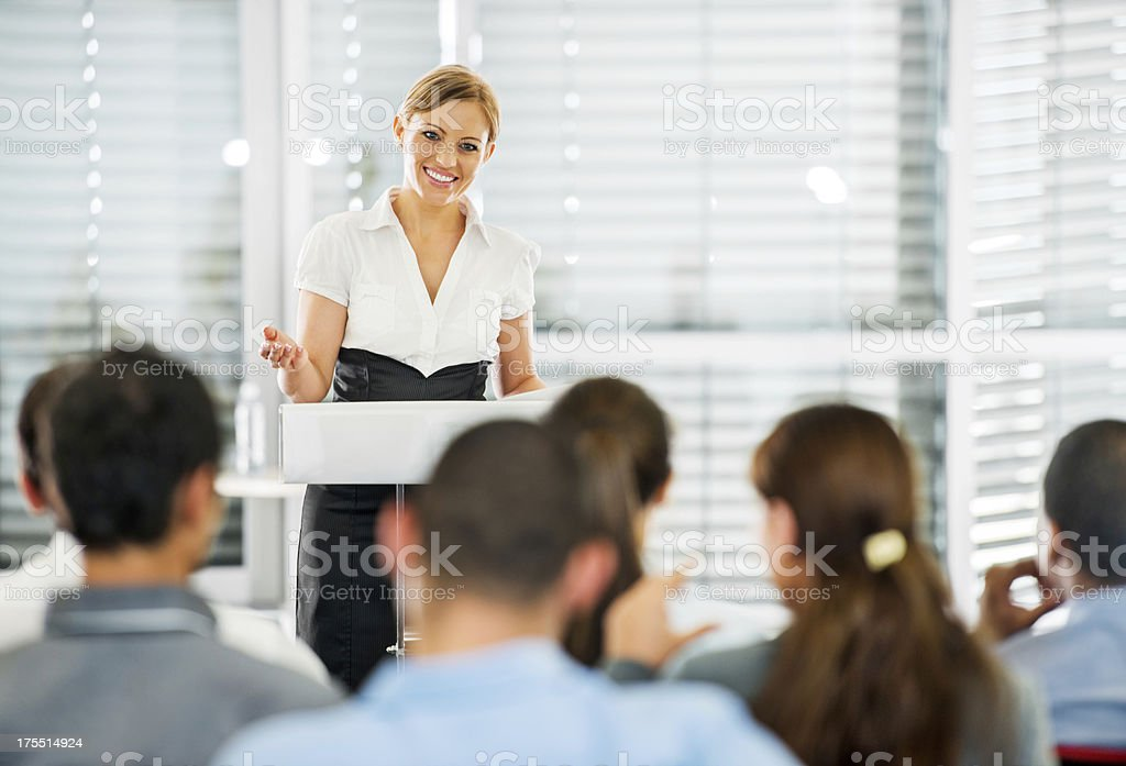 Professional woman giving speech to a crowd stock photo