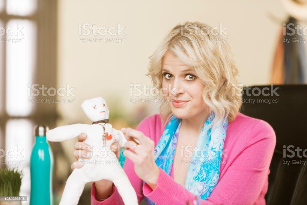 Mulher profissional espetar uma boneca de vudu - foto de acervo