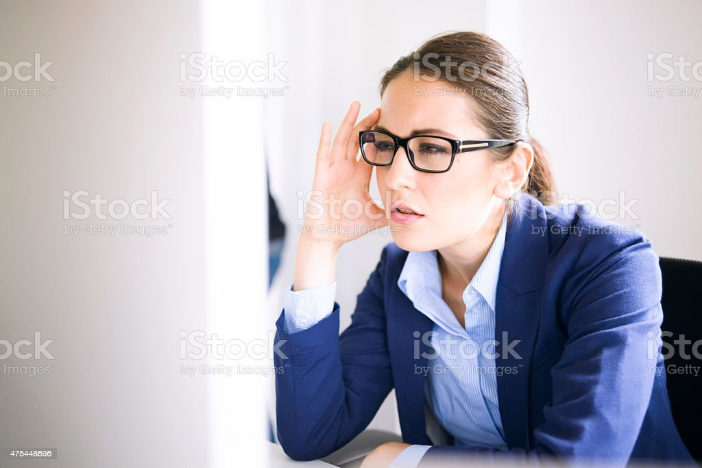 Professional Woman With Glasses Concentrating Deeply on Computer Monitor stock photo