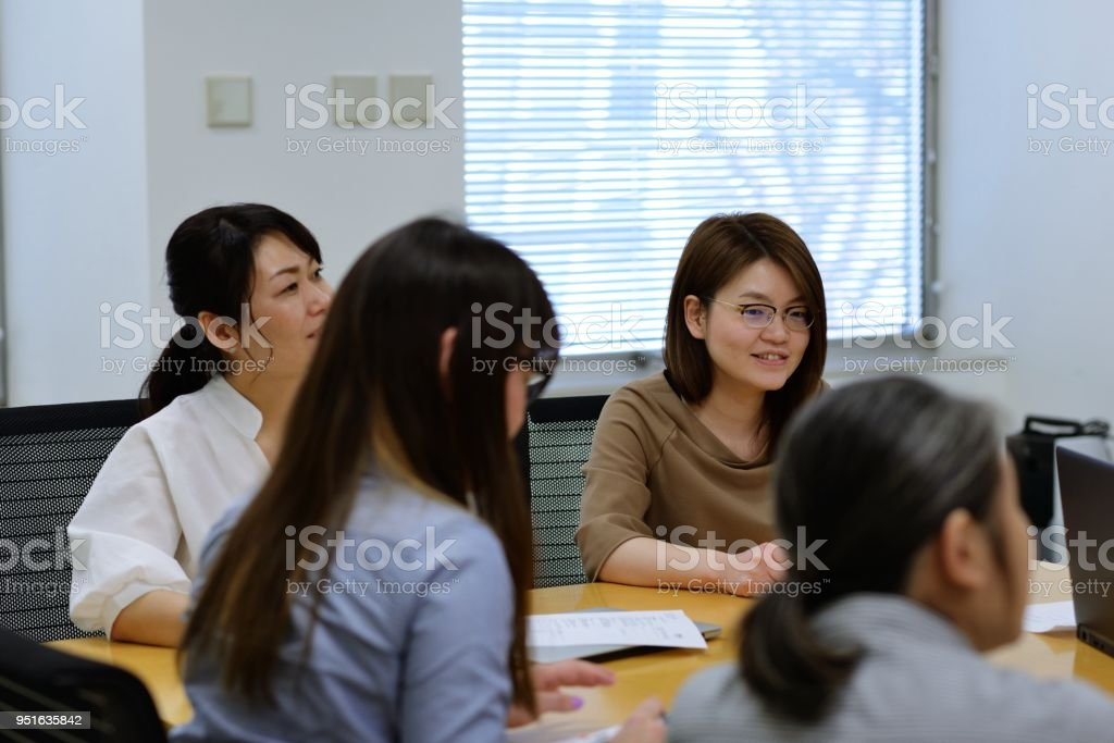 A group of professional women holding a meeting in the office.