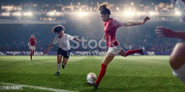 A close up image of a professional women soccer player poised with right leg back about to kick football during a soccer game in a generic floodlit stadium. The player is near opposition players and is wearing a generic red and white soccer kit. With selective focus and bokeh effects.