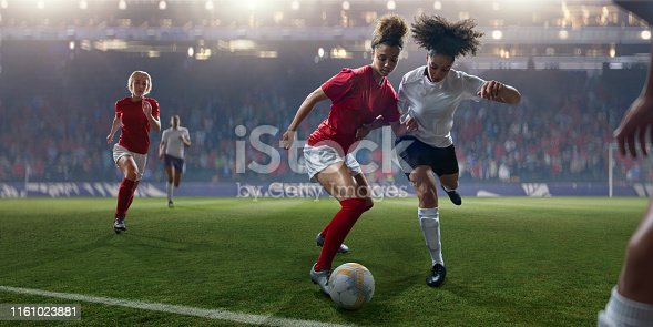 Mid action image of the professional women soccer player dribbling a football whilst being challenged by a rival player. The footballers are wearing generic red and white kit, and white and dark blue kit. The action occurs on a grass soccer pitch in a floodlit stadium full of spectators.