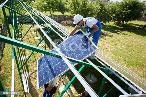 istock Professional worker installing solar panels on the green metal construction 1008853682