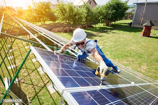 istock Professional worker installing solar panels on the green metal construction 1008854208