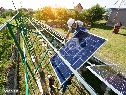 istock Professional worker installing solar panels on the green metal construction 1008854238