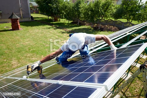 istock Professional worker installing solar panels on the green metal construction 1008854260