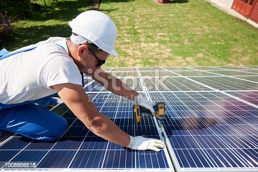 istock Professional worker installing solar panels on the green metal construction 1008856518